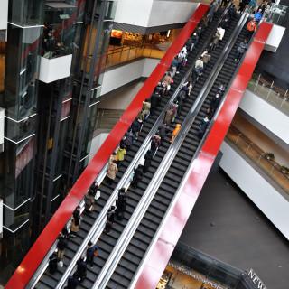 駅ホームと地上間の吹き抜けを横切る真紅の自動式階段 - クイーンズスクエア横浜